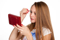Attractive blonde girl does makeup Royalty Free Stock Photo