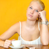 Attractive blonde girl drinking coffee at cafe Stock Images