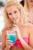 Attractive blonde girl drinks blue cocktail Royalty Free Stock Image