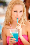 Attractive blonde girl drinks blue cocktail Stock Photography