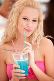 Attractive blonde girl drinks blue cocktail Stock Photos