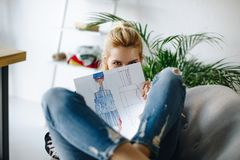 Young fashion designer with sketch. Attractive blonde girl holding fashion sketch and looking at camera Royalty Free Stock Photography