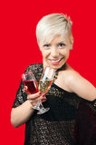 Attractive blonde girl holding glasses of red and white wine. Attractive blonde with short hair in black web shirt holding glasses of red and white wine smiling stock image