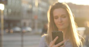 An attractive blonde girl is looking at her phone, blurred close-up portrait and then turns the phone to the camera stock footage