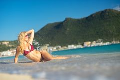 Attractive blonde girl lying down on the beach, fit sporty healthy sexy body in bikini. Freedom, vacation, summertime. Attractive blonde girl lying down on the royalty free stock photo