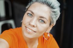 Attractive blonde girl in orange T-shirt making selfie at cafe royalty free stock photography
