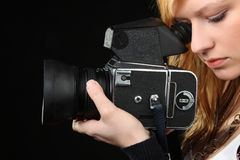 Attractive blonde girl photographing with medium format camera Stock Photography