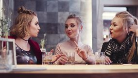 Attractive blonde girl with a ponytail gives a piece of advice to her beautiful friends, while sitting in the bar stock footage