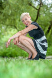 Attractive blonde girl posing in nature crouching Royalty Free Stock Images