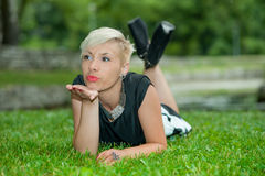 Attractive blonde girl posing in nature lying on grass Stock Photo