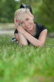 Attractive blonde girl posing in nature lying on grass Stock Photos