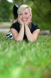 Attractive blonde girl posing in nature lying on grass Royalty Free Stock Images