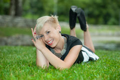 Attractive blonde girl posing in nature lying on grass Stock Image
