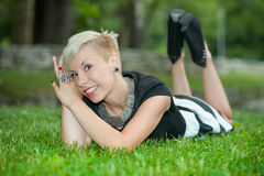 Attractive blonde girl posing in nature lying on grass Stock Photography
