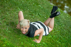 Attractive blonde girl posing in nature lying on grass Stock Images