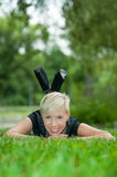 Attractive blonde girl posing in nature lying on grass Royalty Free Stock Photo