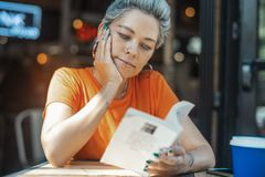 Attractive blonde girl reading book at cafe stock photo