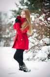 Attractive blonde girl with red coat in winter Stock Photos