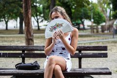 Attractive Blonde Girl Sitting on the Bench in a Park and Hiding. Her Face Behind a Paper Fan Royalty Free Stock Image