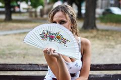 Attractive Blonde Girl Sitting on the Bench in a Park and Hiding. Her Face Behind a Paper Fan Stock Image