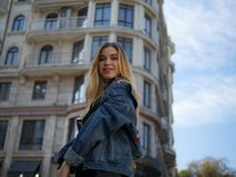 Attractive blonde girl smiling in a denim jacket on the background of a modern building and blue sky stock image