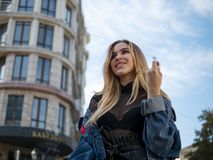 Attractive blonde girl smiling in a denim jacket on the background of a modern building and blue sky stock photography
