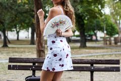 Attractive Blonde Girl Standing in Front of the Bench in a Park. And Holding a Paper Fan Behind Her Back Royalty Free Stock Photography