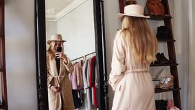 Attractive blonde girl standing in front the mirror in beige coat and trendy hat, making a photo of look with her. Smartphone. Enjoying her style. Footage from stock footage