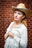 Attractive blonde girl with straw hat and white blouse Stock Photography