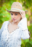 Attractive blonde girl with straw hat and white blouse Royalty Free Stock Photography