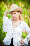 Attractive blonde girl with straw hat and white blouse Royalty Free Stock Images