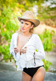 Attractive blonde girl with straw hat and white blouse Royalty Free Stock Image