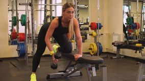 Attractive blonde girl is training with dumbbells in the gym. Attractive athletic blondy female is engaged with dumbbells in gym hard stock video