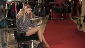 Young woman with new shoes in store. Attractive blonde girl is trying on brand new leather shoes. She is sitting on a comfy chair looking at the shoes stock video