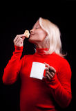 Attractive blonde holding cup and cookies Stock Image