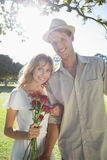 Attractive blonde holding roses standing with partner smiling at camera Royalty Free Stock Photography