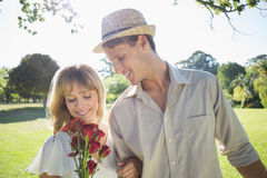Attractive blonde holding roses standing with partner Stock Image