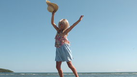 Attractive blonde holding straw hat jumping on the beach Stock Photos