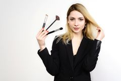 Attractive blonde Make-up artist holding brushes. On white background Royalty Free Stock Photos