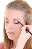 Attractive blonde with make-up brush over white Stock Photo