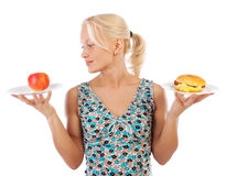 Attractive blonde making choice. Portrait of happy girl making choice between burger and apple Royalty Free Stock Photos