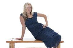 Attractive blonde model in blue dress on bench with an attitude Stock Photos