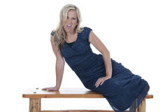Attractive blonde model in blue dress on bench with an attitude Royalty Free Stock Photo