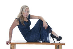 Attractive blonde model in blue dress on bench looking at camera Stock Images
