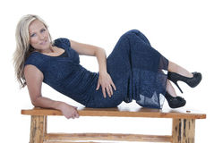Attractive blonde model in blue dress on bench smiling Stock Photo