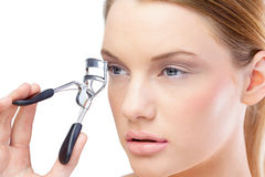 Attractive blonde model using eyelash curler Royalty Free Stock Photos