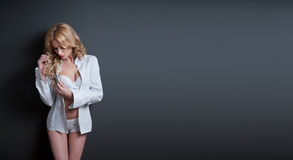Attractive blonde model with white bra, shirt and shorts standing on gray background. Fashion portrait of a cute blonde girl Stock Photo
