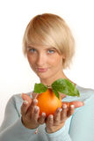 Attractive blonde with an orange Royalty Free Stock Image