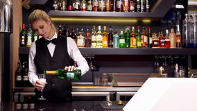 Attractive blonde pouring champagne at the bar stock video