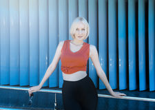 Attractive blonde in red top and black leggings posing against s stock images
